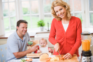Woman slicing carrots and man feeding baby
